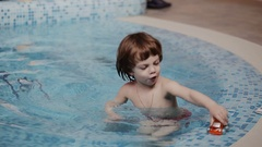 Mom and son playing in the pool with toys Stock Footage