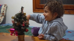 Cute kid thinks and artificial tree Stock Footage