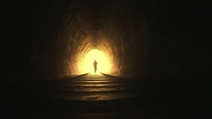 Silhouette of man running toward camera inside dark railway tunnel slow motion Stock Footage