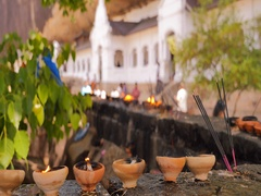 Burning candles and praying sticks outside of Dambulla Buddhist cave temple Stock Footage