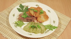 Man eating dish of potatoes with roasted meat Stock Footage