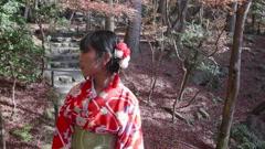 Japanese girl wearing kimono walking through temples gardens steadycam shot Stock Footage