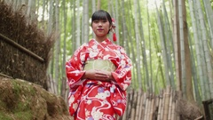 Japanese Kimono girl welcomes tourists to Bamboo forest in Kyoto Japan  Stock Footage