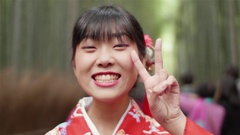 Happy japanese kimono girl pece sign in Bamboo forest Kyoto Japan  Stock Footage