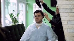 A man at barber's. Blonde hairdresser drying the men's head using hairdryer. HD Stock Footage