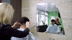 Female blonde hairdresser cutting hair of dark-haired man at beauty parlour. HD Stock Footage
