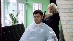 A man at hairdresser's. Female barber drying the men's head using hairdrier. HD Stock Footage