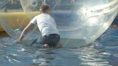 Little child inside a big inflatable ball in water Stock Footage