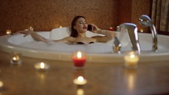 Woman in bath with foam talking on phone Stock Footage
