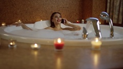Woman lying in bath near candles and talking on phone Stock Footage