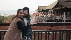 Excited tourists in Kyoto pose in front of famous landmark temple Kyoto Japan Stock Footage