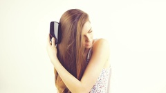 Beautiful woman brushing and touching long silky hair isolated Stock Footage