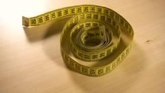 Yellow measuring tape spinning around Stock Footage