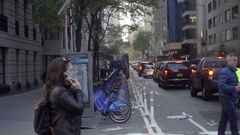 Citi bike station woman on cell phone crossing street zooming out taxi cab NYC Stock Footage