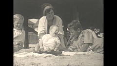 Vintage 16mm film, 1927 roaring 20s, family at beach, baby tips over Stock Footage