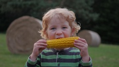 Young blonde child with curly hair eating corn on the cob Stock Footage