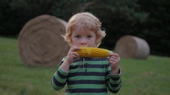 Boy eats corn off of the cob and smiling Stock Footage