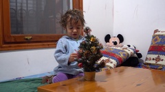 Three years old boy and artificial New Year Tree Stock Footage