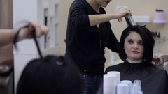 Hairdresser straightening black hair with hair irons. Stock Footage
