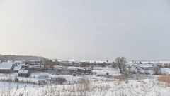View of typical Russian village at winter - cold day in snow-covered field Stock Footage