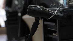 Close-up shot of hairdresser takes a hairdryer Stock Footage
