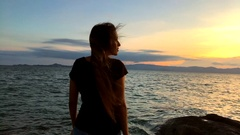 Young happy asian girl spreading arms at beautiful sunset. Slow motion back view Stock Footage
