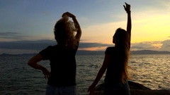 Two young happy girl having fun and spreading arms at beautiful sunset. Slow Stock Footage