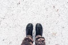 Male feet in leather shoes standing in snow from above Stock Photos