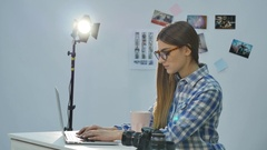 Pretty young woman photographer working with laptop and drinking coffee in the Stock Footage