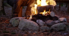 Man using compass and smart phone by campfire in the woods Stock Footage