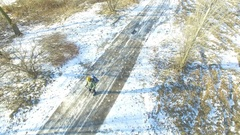 4K Aerial. Man hiker with  backpack goes  on  frozen road in winter . Low heigh Stock Footage