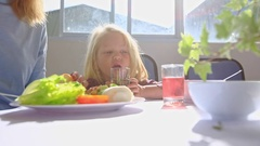 Little Blonde Girl Sits at Table Drinks Juice Near Mother Eating Breakfast Stock Footage