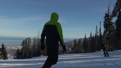 Snowboarder going ski slope on sunny winter day Stock Footage