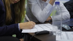 Young girl filling in an application form of participant of business game Stock Footage