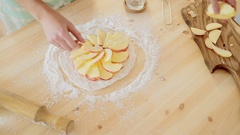 Woman makes apple pie in her kitchen. Hands puts apples on the dough. Stock Footage