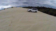 4x4 Vehicle driving up a steep sand dune Stock Footage