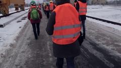 People in work helmet and reflective vest walks Stock Footage