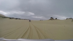 4x4 Vehicle following car over sand dune in rain Stock Footage