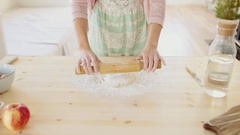 Baker kneading dough with rolling pin on wood table at home Stock Footage