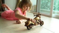 5 year old girl play with toy wooden motorcycle 4K Stock Footage