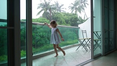 5 year old girl having fun on the balcony during a heavy tropical rain 4K Stock Footage