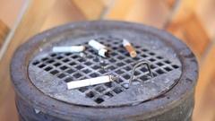 Smoldering cigarettes in the street metallic ashtray Stock Footage