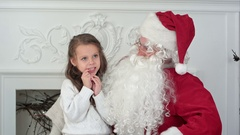 Santa Claus sitting in a chair with a little girl dreaming about her Christmas Stock Footage