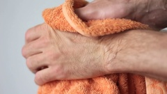 Wiping hands with an orange towel Stock Footage