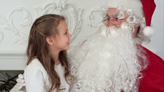 Sweet little girl on Santa Claus lap telling him what she wants for Christmas Stock Footage