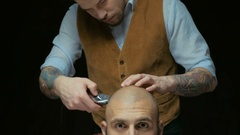 Close-up of a man getting his hair shaved with trimmer. Hairdressers hand is Stock Footage