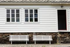Symmetrical two white bench in front traditional house. Stock Photos