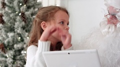 Santa with tablet listenting to a little girl describing presents she wants for Stock Footage