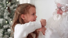 Little girl showing Santa Claus a magic trick with a disappearing finger Stock Footage