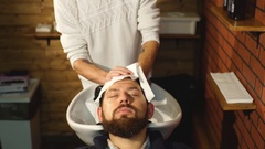Hairstylist washing client's hair in barber shop Stock Footage